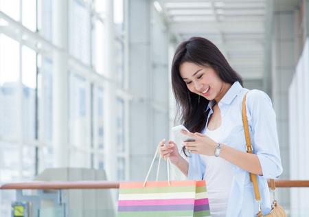 幸せな若いアジア女性はショッピングします。