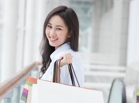 Happy young Asian woman shopping. photo