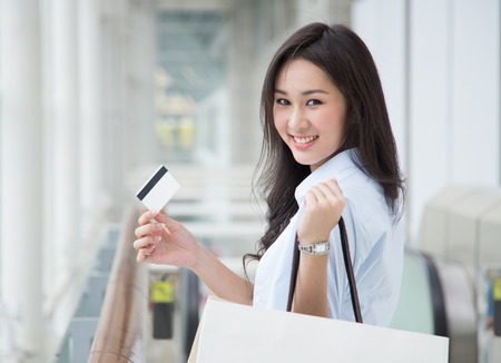 Asian woman holding shopping bags and a card photo