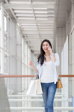 Woman using her phone while shopping photo