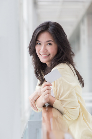 Mujer asiática que sostiene una tarjeta en la mano