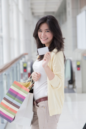 shopping card: Asian woman holding a card in her hand