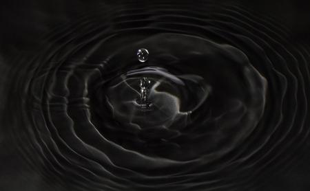Wassertropfen fällt auf schwarzem Wasser Standard-Bild - 41889450