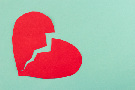 broken up: close up of paper broken heart on blue background