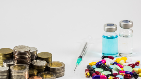 to restrain: Medicine with money and syringe on white background. Expensive bill. Finance concept of pharmacy business. Stock Photo