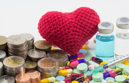 healthcare cost money coins and bills with medicine, vaccine and big red heart