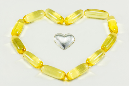 palliative: pills in heart shape and silver heart Stock Photo