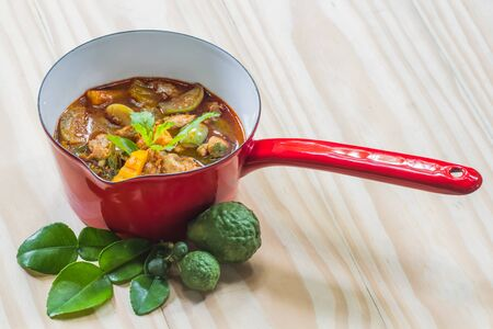 green vegetables: pork red curry on the red pot, delicious thai food Stock Photo