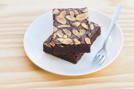 repast: pieces of chocolate brownie cake on a wooden background