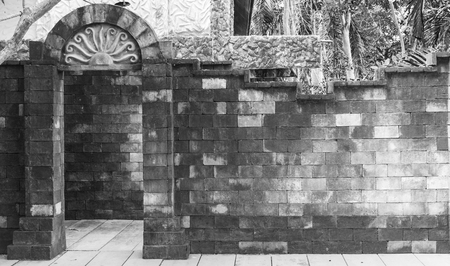unyielding: brick door and wall on black and white