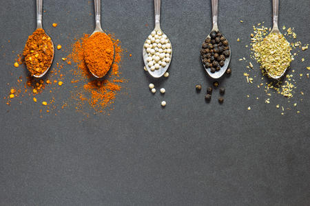repast: five type of spices and herb on the spoon on black stone background Stock Photo