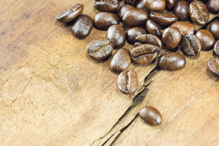 gluttonous: Coffee Beans  texture  on the wood background,selective focus,worm toning Stock Photo