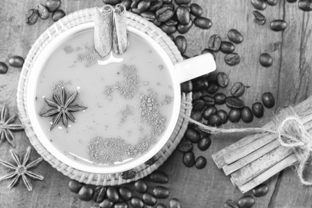gluttonous: coffee on the cup with coffee beans and cinnamon sticks on wood background on balck and white, selective focus Stock Photo
