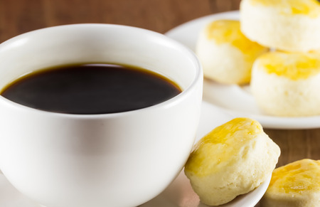 kopi: a cup of coffee and scone on wood background, warm toning, selective focus Stock Photo