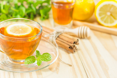 crave: tea with mint honey cinnamon and lemon on wood background,warm toning, selective focus Stock Photo
