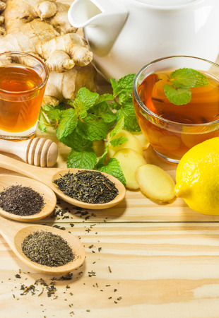 gluttonous: tea with mint honey ginger and lemon on wood background,warm toning, selective focus