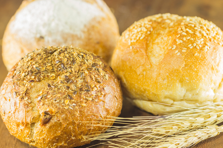 repast: bread and wheat on the wood background, warm toning, selective focus