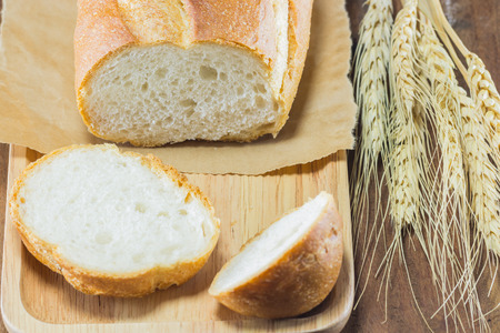 gluttonous: bread and wheat on the wood background, selective focus