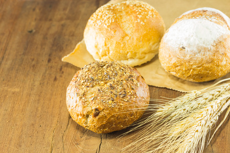 gluttonous: bread and wheat on the wood background, warm toning, selective focus
