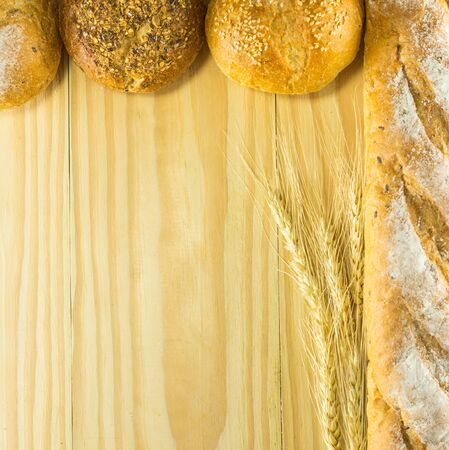 crave: bread and wheat on the wood background, warm toning, selective focus