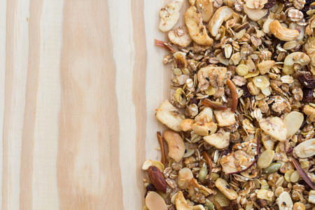 crave: Pile of granola cereal on the wood background