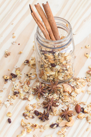 gluttonous: Pile of granola cereal and cinnamon sticks on the wood background Stock Photo