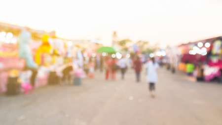 vend: abstract blur background of people shopping at market fair with sunlight