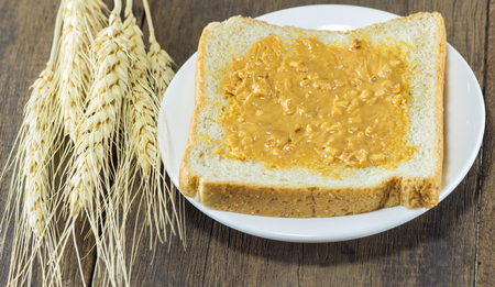 lambent: selective focus of bread and peanut butter on wood background with wheat