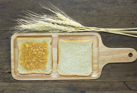 pellucid: selective focus of bread and peanut butter on wood background with wheat