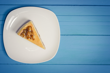 aliment: macadamia cheesecake topping with caramel on white plate on blue wood background,vintage toning Stock Photo