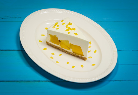 split up: close up of mango cream pie with peeled split mung bean on white plate and blue wood ,vintage toning Stock Photo