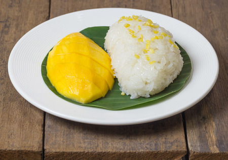lambent: mango sticky rice with peeled split mung bean on white plate Stock Photo
