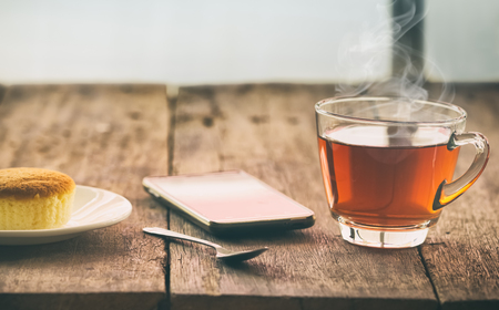 pellucid: hot tea cup with butter cake and smartpho on the table on the winter day, vintage toning