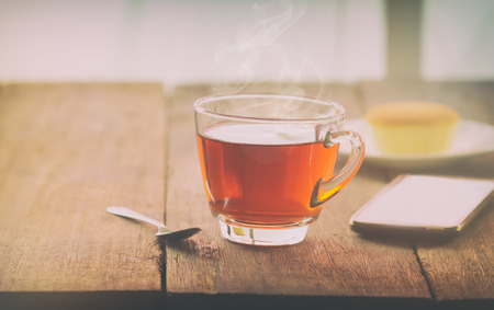 lucid: hot tea cup with butter cake and smartpho on the table on the winter day, vintage toning
