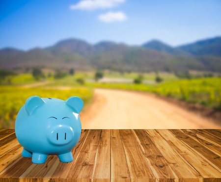 blue pig bank on wooden table with blur stock market background,money and saving concept.