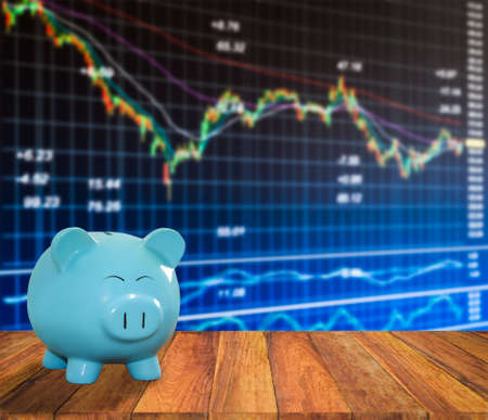 lucid: blue pig bank on wood background with blur stock market background,money and saving concept.
