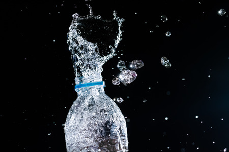 to flit: Water splashes from the bottle on black background
