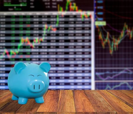 lambent: blue pig bank on wood background with blur stock market background,money and saving concept.