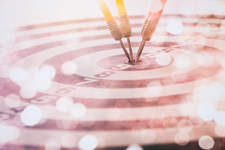 Arrows on dart board with bokeh background mean the goal and success. Suitable for all artwork design about marketing target and business which want to relate for victory concept. 스톡 콘텐츠