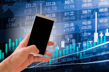 Hand hold smart phone on stock market indicator and financial data background for your design. Double exposure financial graph and stock indicator. Abstract stock market financial indicator background