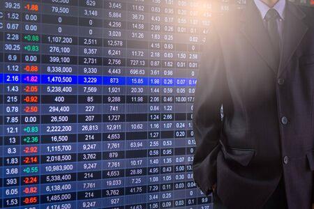 Business man on stock market financial trade indicator background. Man analysis stock market financial trade indices on LED. Double exposure of business man trade on stock market financial concept.