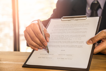 Geschäftsmann, der einen Vertrag unterzeichnet. Besitzt das Geschäftszeichen persönlich, Direktor des Unternehmens, Rechtsanwalt. Immobilienmakler, der Haus, Finanz- oder Mieteigentum, Fusions- und Akquisitionskonzept hält. Standard-Bild