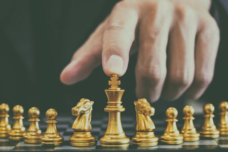 Chess game on chess board behind business man background. Business concept to present financial information and marketing strategy analysis. Investment target in global economy and digital commercial. Stock Photo