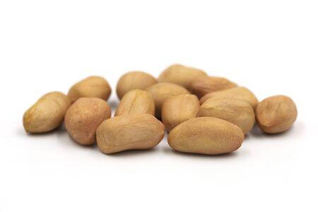 Heap raw organic peanut with peel on white background and copy space. Peanut is one of 8 allergens foods but have high protein and high nutrition delicious taste. Food and nuts concept.