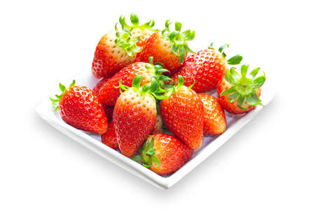 Organic ripe korean strawberry heap on white plate on white isolated background with clipping paths. Prepare fresh strawberries for salad cooking and dessert. High vitamin and healthy fruits concept.