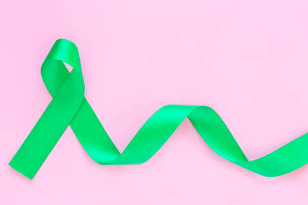 Emerald green or jade green ribbon curl on pastel pink background with copy space, symbol for Liver Cancer awareness, World Cancer Day. Healthcare or hospital and insurance concept.