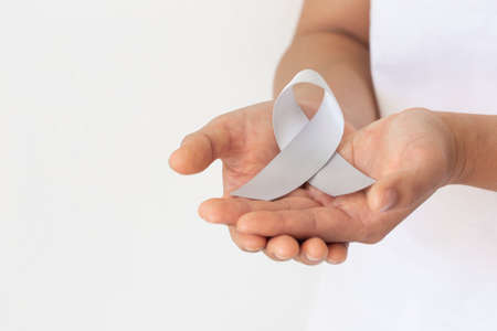 Hand holding Gray ribbon on white fabric