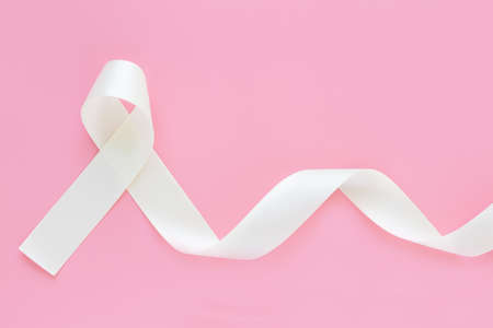 White pearl ribbon curl on pink isolated background with copy space. Lung Cancer Awareness, Mesothelioma and Retinoblastoma cancer symbol. Purity sign for Anti-violence against women, safe motherhood. Standard-Bild