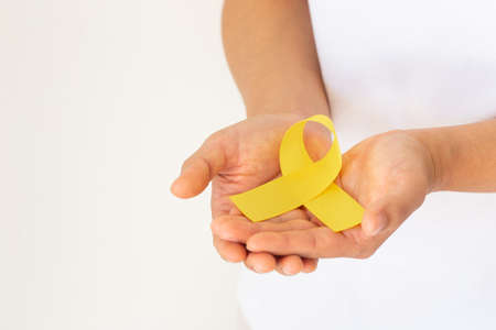 Hands holding gold ribbon on white isolated background with copy space. The international awareness symbol for Childhood Cancer. World Cancer Day. Healthcare or hospital and insurance concept.