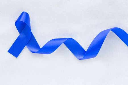 Deep blue ribbon curl on white fabric with copy space. Colorectal Cancer Awareness, Colon cancer of older person and world diabetes day, Child abuse prevention. Healthcare, insurance concept.